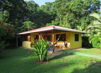 บ้านชั้นเดียวหลังเล็กๆ รูปทรงตัวแอล L ผูกเปลญวนนอนหน้าบ้านได้